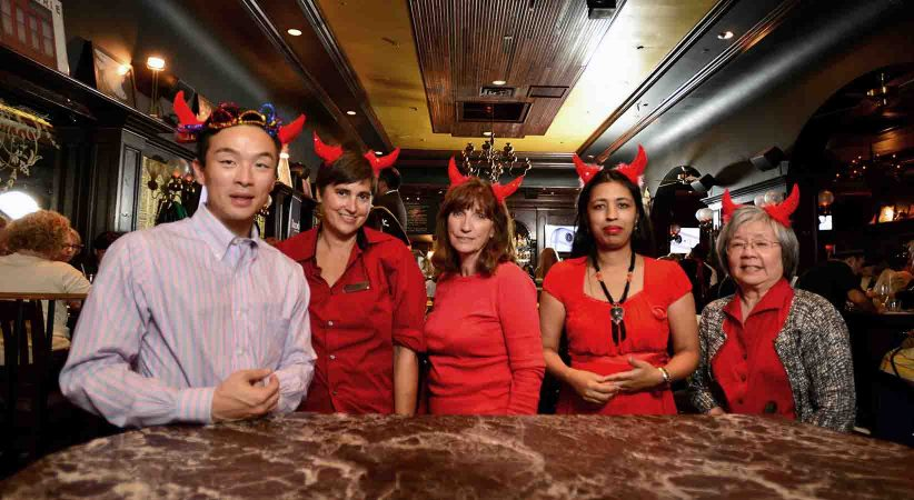 Four women and one man stand at a table wearing red devil horns.