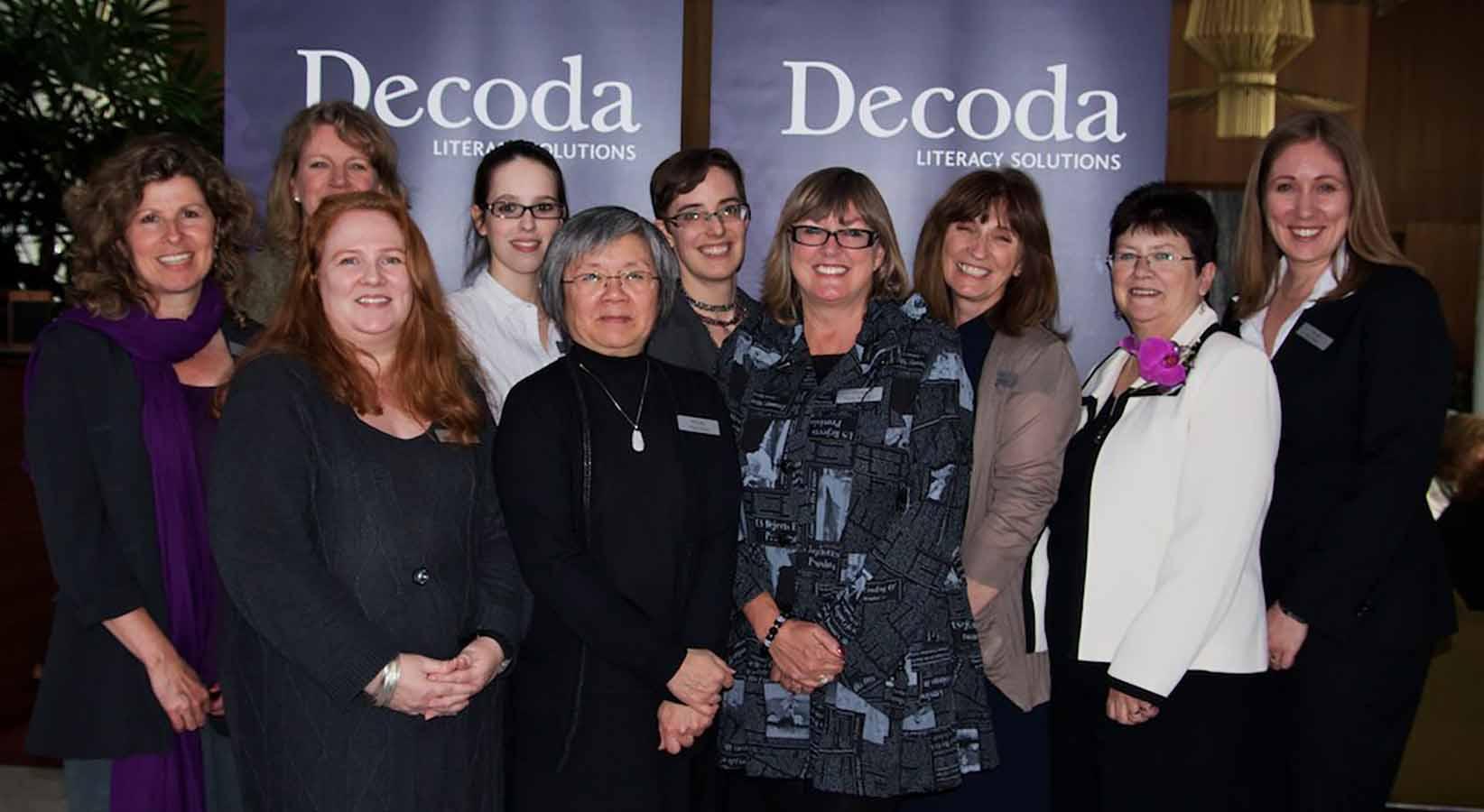 Ten women standing in front of a Decoda sign