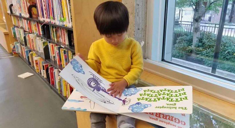 Preschooler reading book in a library