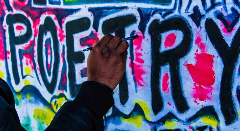"""A hand writes the word """"poetry"""" on a wall of graffiti."""