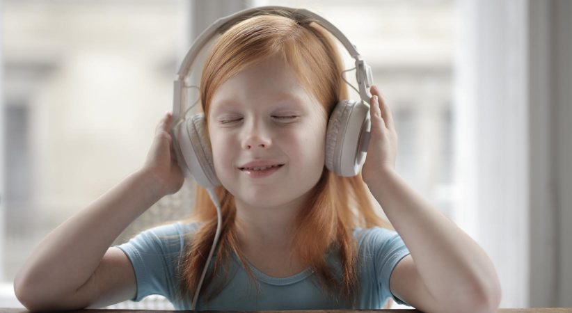 Girl listens to headphone with her eyes closed.