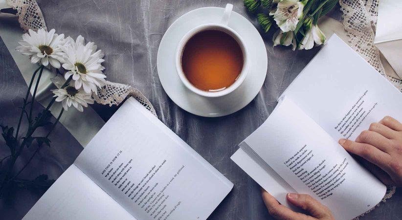 two open poetry books and a cup of tea on a table. Two hands hold one book open.
