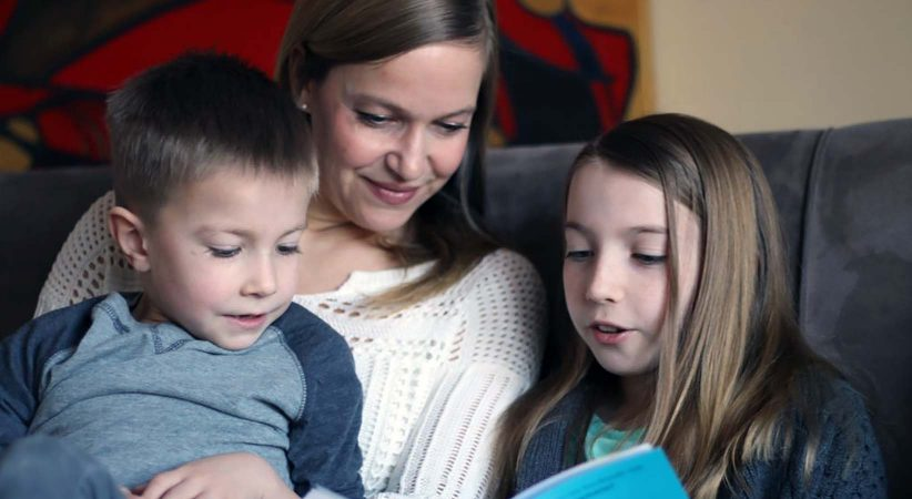 Women reads a book with two children