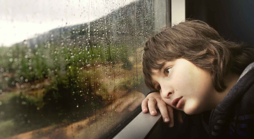 A boy stares out of a rain-washed window.