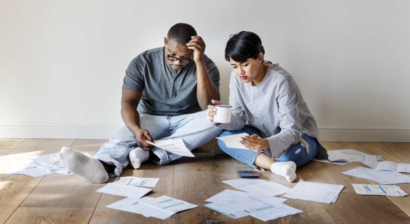 A couple sits on the floor surrounded by paperwork.