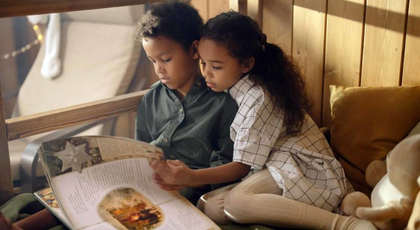 Two children read a picture book on a bed.