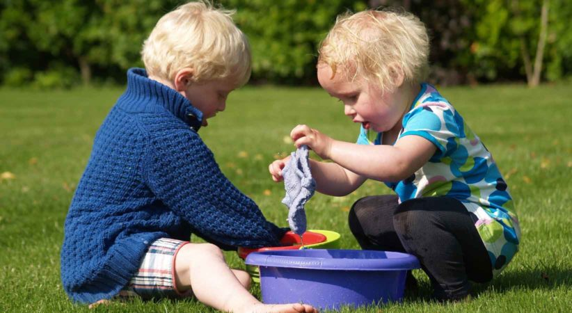 two children playing with buckets on the grass.