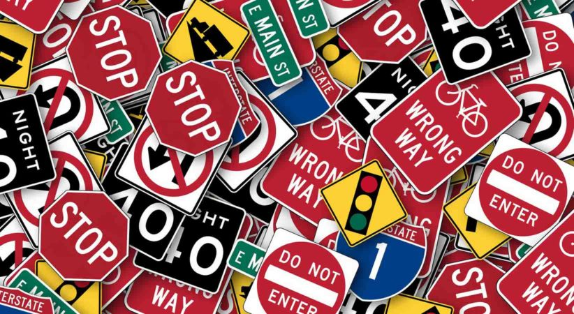 A collection of road signs piled on top of each other.