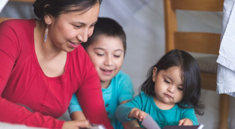 Indigenous woman reads with two children.