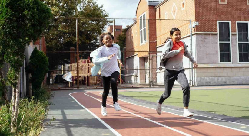 Two children run along a track beside a brick building.