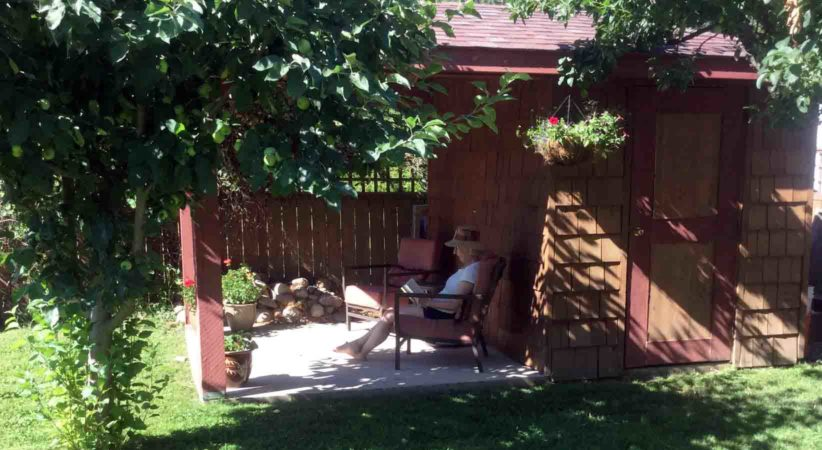 A woman reads a book in the shade on a porch.
