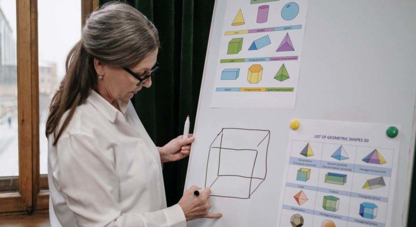 teacher drawing geometry diagram on whiteboard