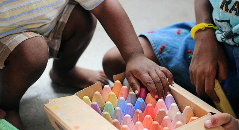 Child reaches for large chalk pieces while adult sits to the side.