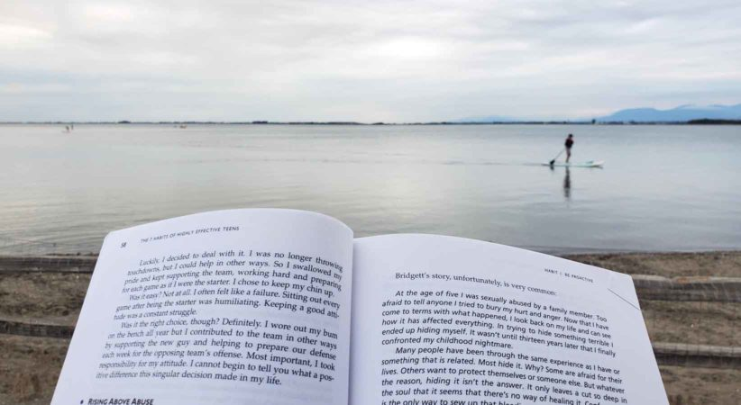 An open book held in the foreground with a beach, water and a paddleboarder in the background.