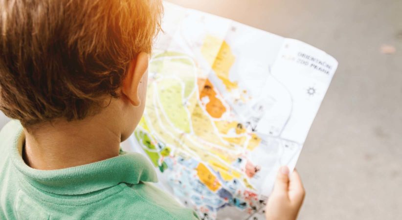 A child holds a colourful map in their hands.