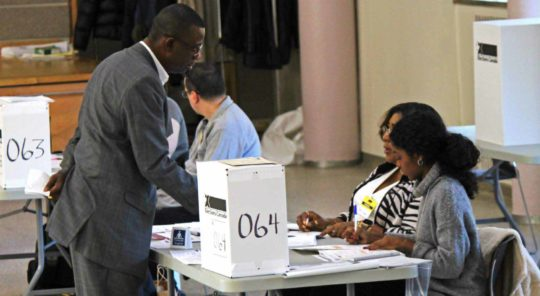 A man stands at a voting station with two women seated at the table.