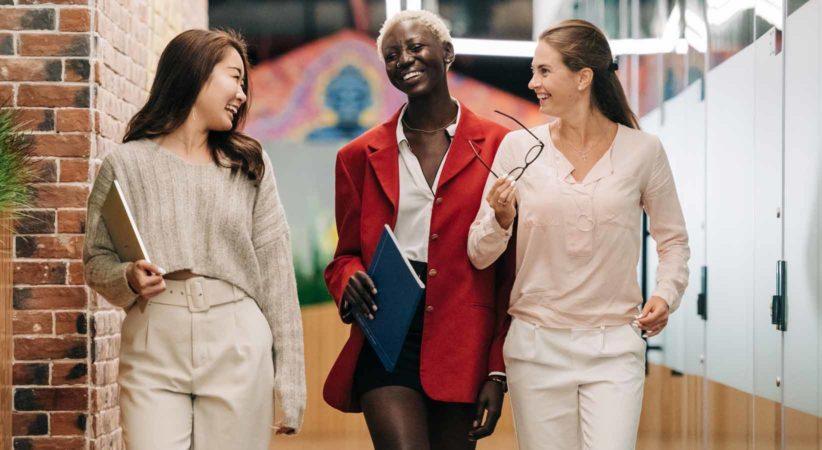 Three women walking down a hallway smiling