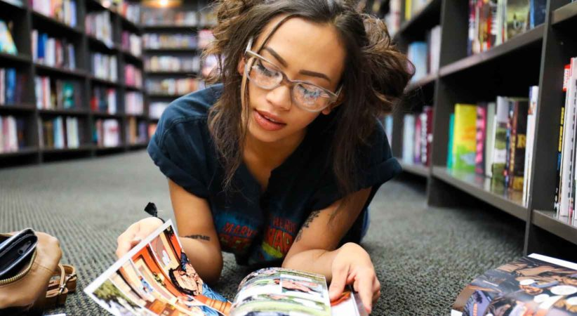 Woman lying on her stomach reading a comic books on a library floor