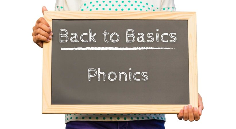 """Person holding chalkboard which reads, """"Back to Basics: Phonics"""""""