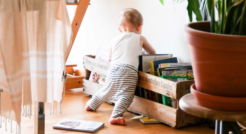 A baby looking through a bin of books