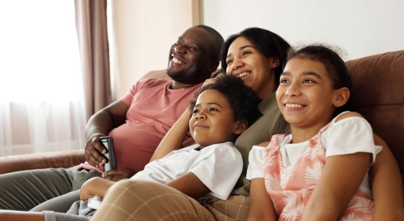 Two adults and two children sitting on a couch watching a movie.