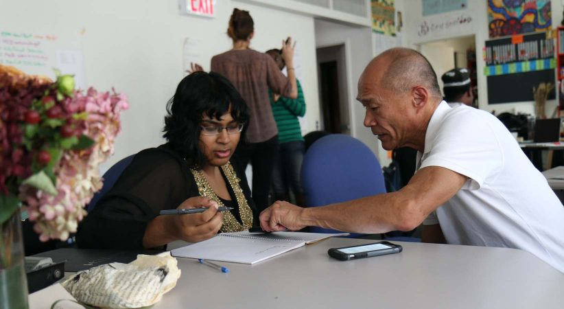 Man helping a woman fill out paperwork