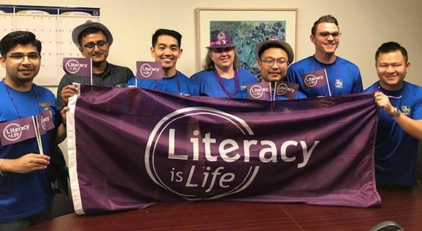 """A group of people hold a """"literacy is life"""" flag"""