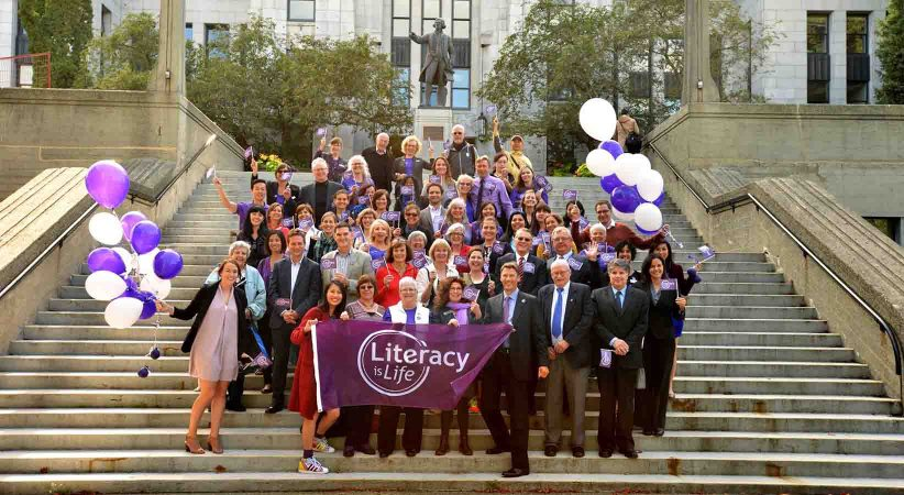 """Crowd stands in front of Vancouver City Hall holding purple """"Literacy is Life"""" banner"""