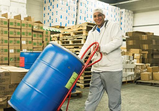 Man wheeling a barrel in a warehouse