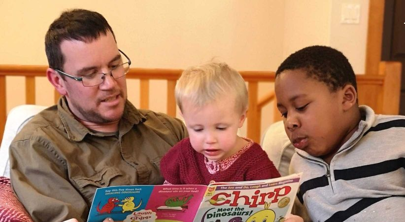 A man reading to two children