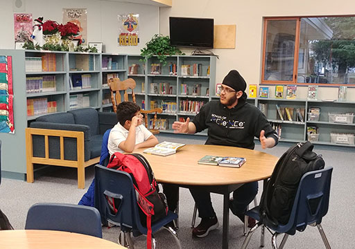 Man speaking to boy at a library table