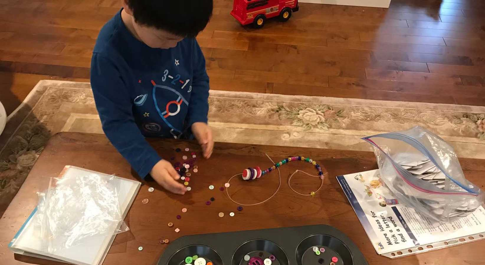 Lin Dong's son Henry counting button on a table.