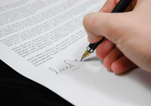 Hand signing document with pen