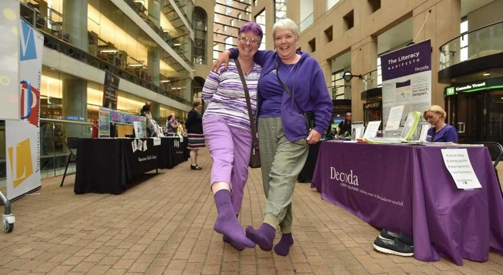 Two women stand with arms around each other holding out their feet with Sock it To Literacy socks on.