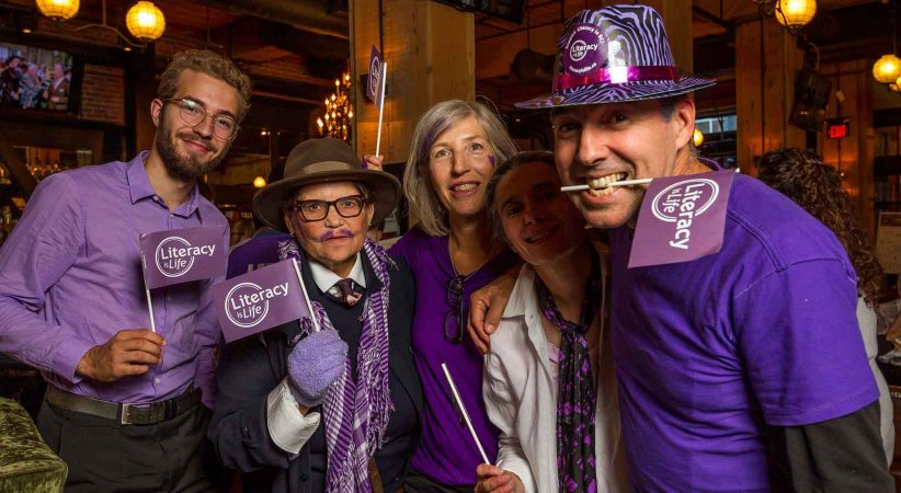 Four people at an event dressed in purple