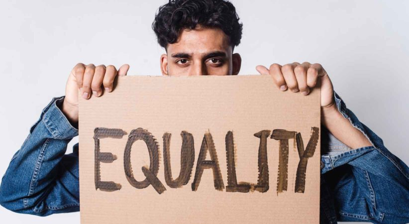 """man holds up a sign that says, """"equality""""."""