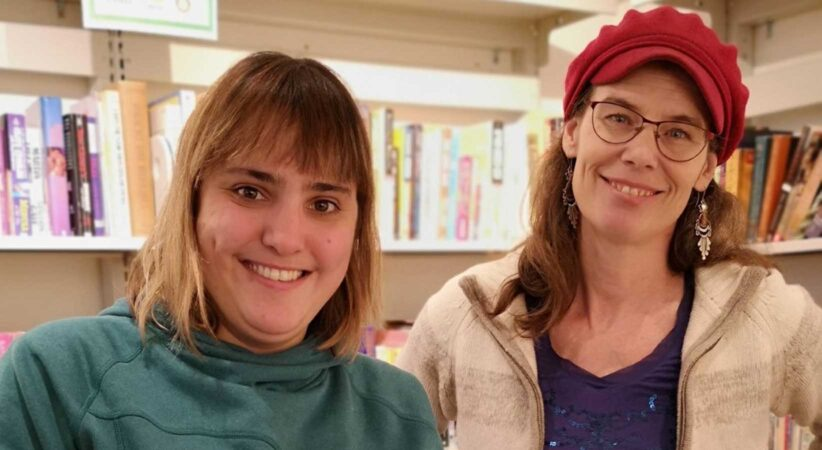 Two women stand side by side in a library