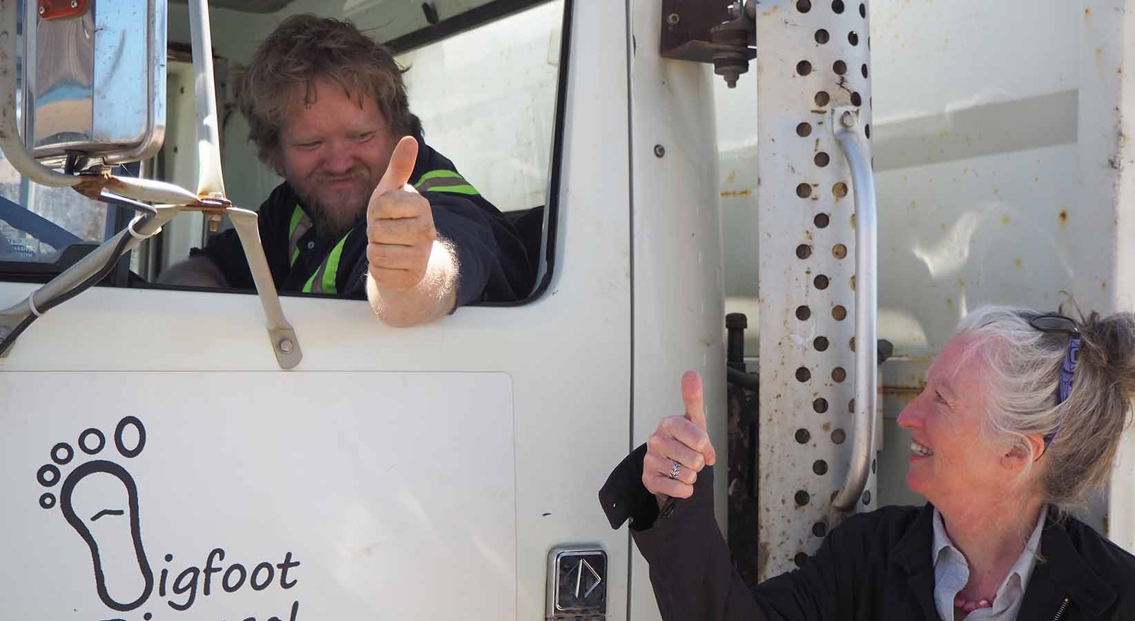 A man in a truck gives a woman an thumbs up