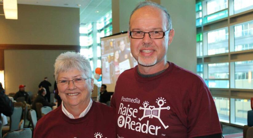 A man and a woman stand side by side wearing Raise A Reader t-shirts.