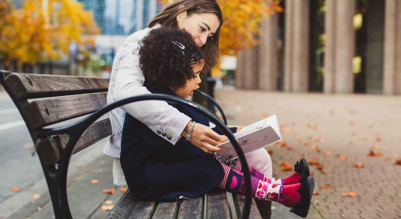 Woman and child reading on a bench