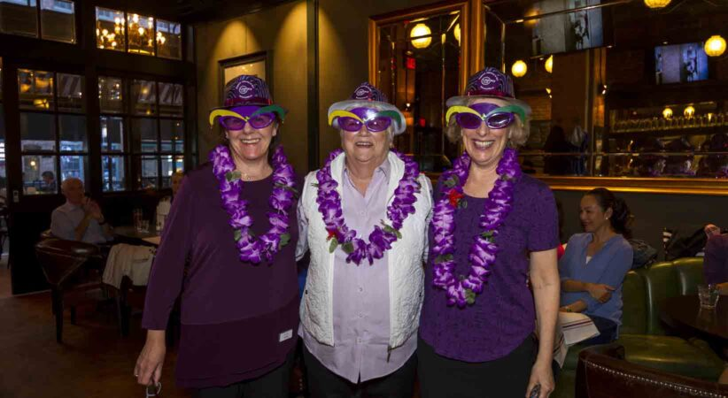 Three ladies stand together wearing purple hats, novelty glasses and leis.