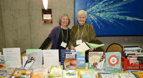 Two women stand behind a table full of books.