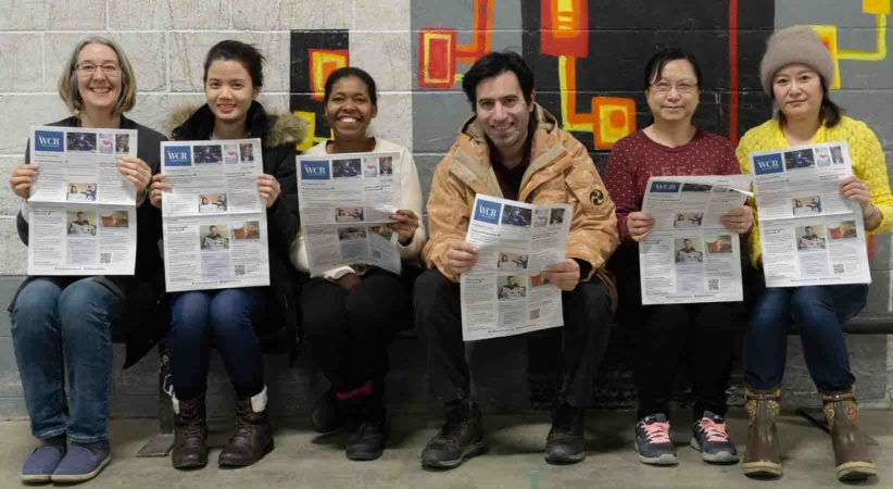 Six adults facing the camera, sitting and holding a newspaper.