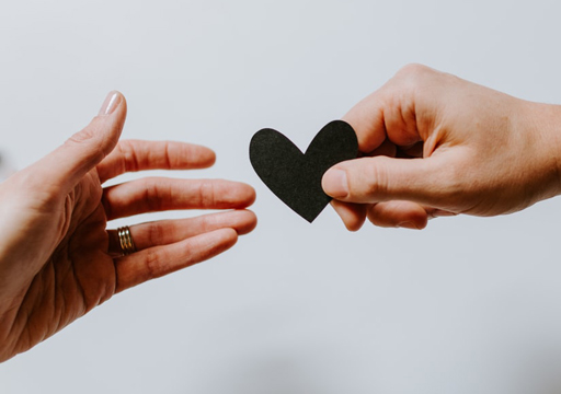 Hand receiving a heart from another hand