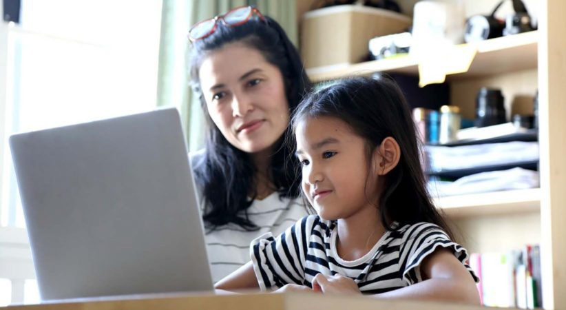 A woman and a child looking at a laptop screen.